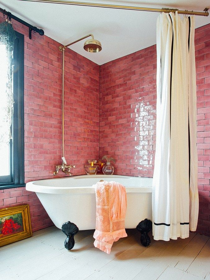 Pink subway tiles with soft accents and gold fixtu…