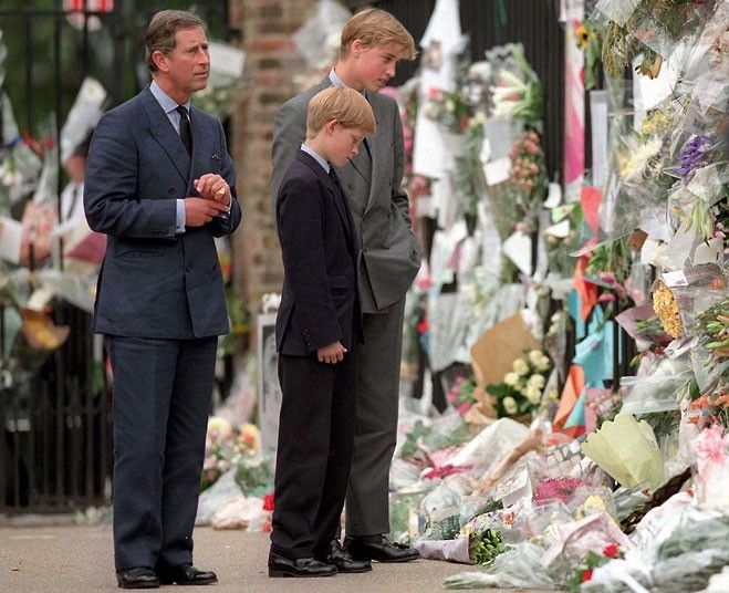 September 1997: Prince Charles, Prince William and Prince Harry look at floral tributes left at Kensington Palace after the death of Princess Diana