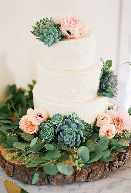incorporation of lush green succulents with pale pink peonies, dahlias, and ranunculus