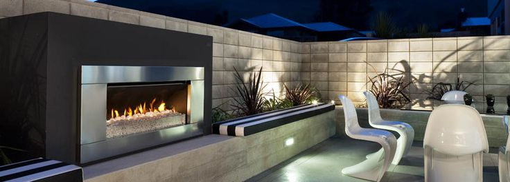 Escea EF5000 gas fireplace in landscaped outdoor area with dinning set at night