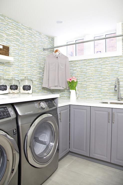 Boasting walls clad in green and glass tiles, this stunning green and gray contemporary laundry room features a curved stainless steel sink with a polished nickel gooseneck faucet fixed to a white quartz countertop accenting gray cabinets fitted with satin nickel pulls.