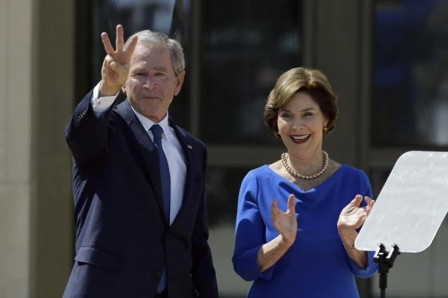 Former President George W. Bush, accompanied by his wife former first lady Laura Bush, flashes the W sign after his speech during the dedication of the George W. Bush Presidential Center.