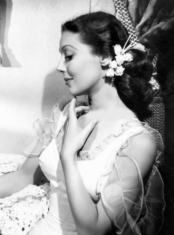 Loretta Young with flowers tucked in to the side of her hair, early 40s