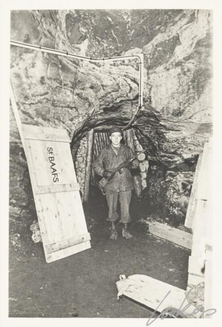 Een Amerikaanse soldaat bewaakt de ingang van één van de kamers in de zoutmijn van Alt Ausee. Aan het begin van de Tweede Wereldoorlog werden de panelen van het retabel van het Lam Gods vanuit Gent per vrachtwagen naar de Franse stad Pau overgebracht. Na 9 reisdagen kwam het werk er aan op 26 mei 1940. Ruim twee jaar konden de panelen er uit de handen van de Duitse bezetter blijven. Maar, op 3 augustus 1942 roofden de Duitsers de panelen en brachten ze over naar het Beierse slot ...