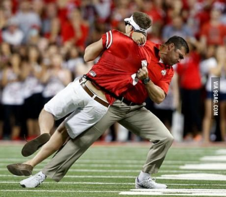 During the Ohio State football game, someone ran out onto the field. One of the Ohio State coaches stopped him.