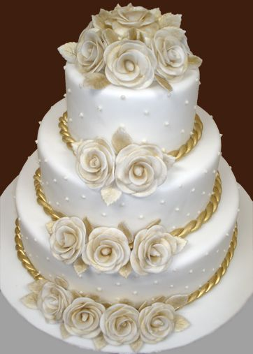 white and gold wedding cake.. LOVE... love the roping around the borders of the cake.  Maybe change the flowers to yellow and get rid of the gold border and make red?  Jeanette?