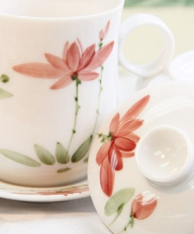 This hand-painted embossed lotus cup represents the delightful yet subtle temperament of a warm home. The cup, plate, and lid cover is made of bone china.