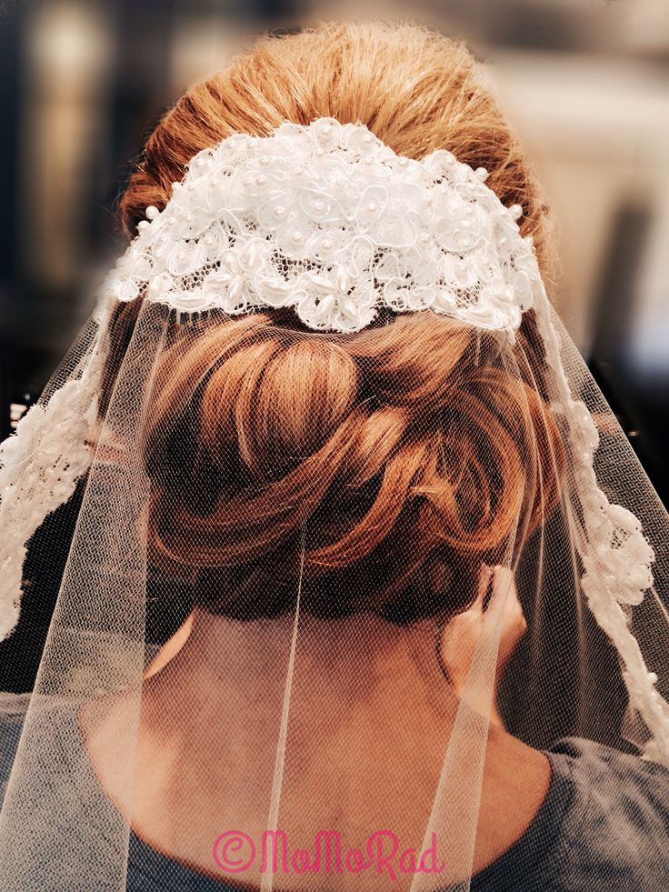 loose curls pinned back in a classic bridal updo with a lace veil
