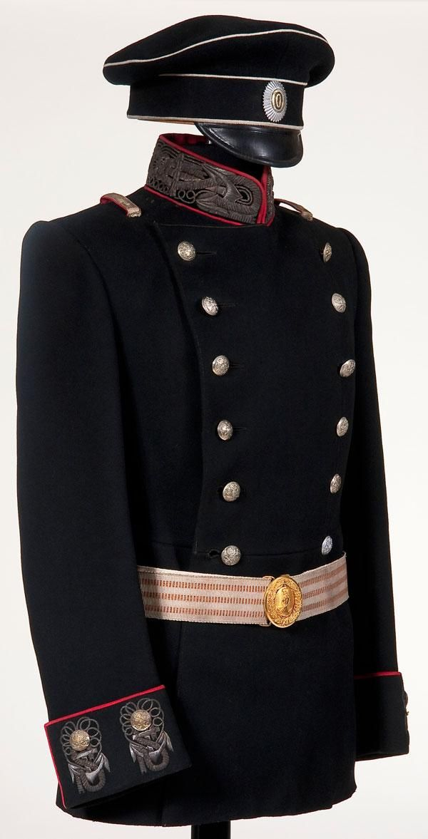 Imperial Russian Navy officer's uniform group, including tunic, cap and belt,circa 1910.  Black wool double breasted tunic with red piping and richly embroidered silver bullion anchor motifs on the collar and cuffs. Visor cap of black wool with white piping and black leather visor, with officer's pattern cockade on the band. Group also includes a silver brocade belt with mixed orange and black, and a gold spoon and wreath Navy buckle.