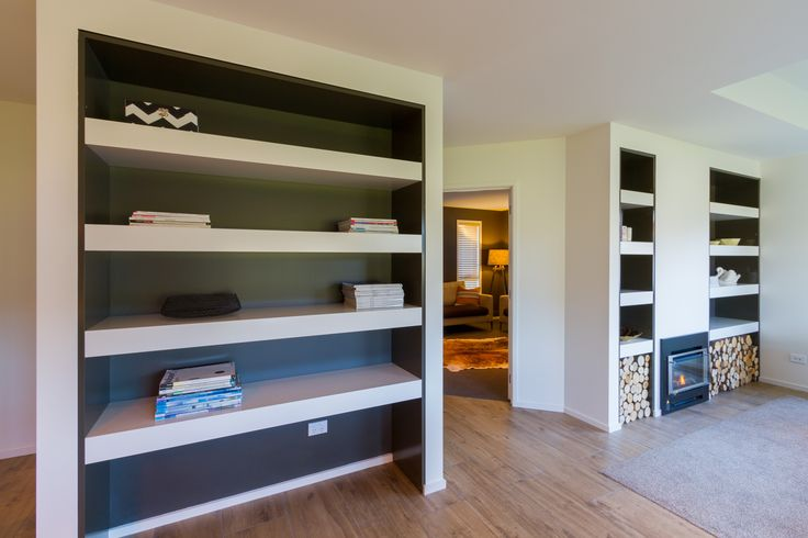 Beautiful built-in bookcase with a modern fireplace between two neat firewood cabinets. While the closed off family room behind looks inviting.