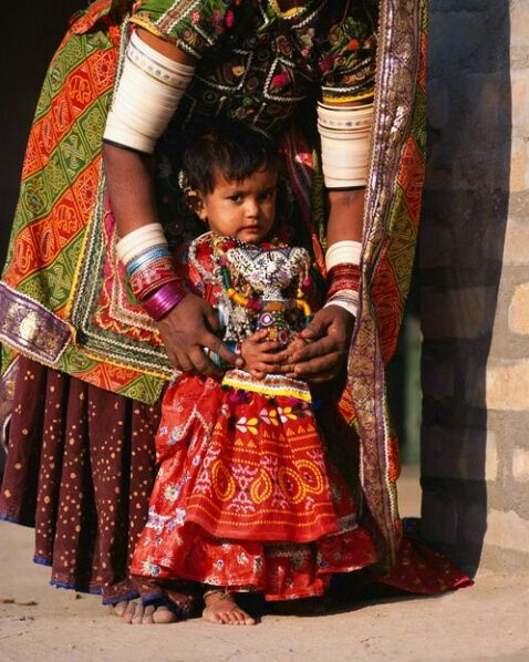Colorfull traditional dressed Mother and child, Meghwar tribe, Gujurat, India  by Jim Zuckerman