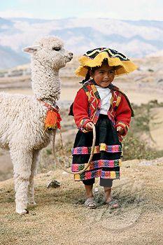 Niña peruana de los Andes con una joven alpaca.