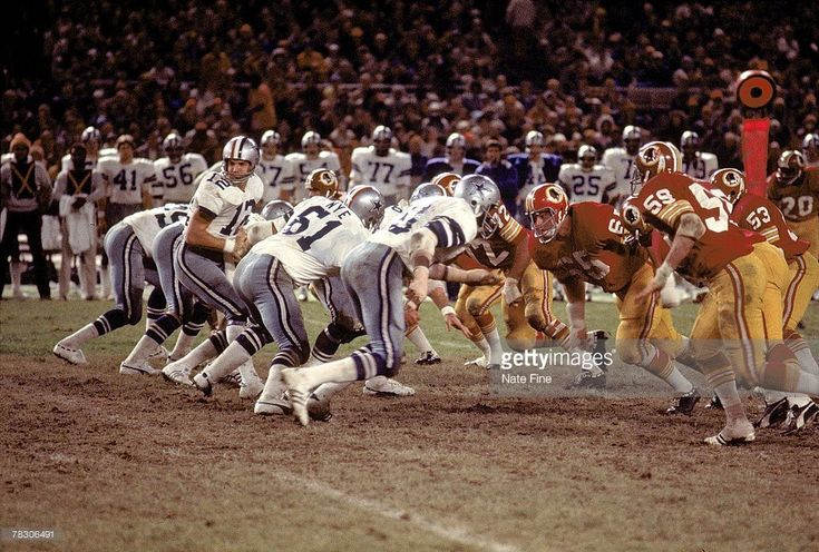 Quarterback Roger Staubach #12 of the Dallas Cowboys turn to handoff against the Washington Redskins at RFK Stadium on October 31, 1976 in Washington, D.C. The Cowboys defeated the Redskins 20-7.