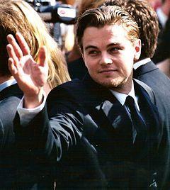 Leonardo DiCaprio is rising his hand.
