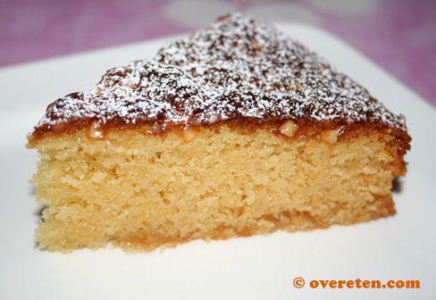 Marsepein-sinaasappelcake (ingrediënten: suiker, marsepein/amandelspijs, roomboter, amandel extract, ei, sinaasappelrasp, patentbloem, bakpoeder, zout, geschaafde amandelen en evt. gekonfijte sinaasappelschil en poedersuiker) (@ Over Eten)