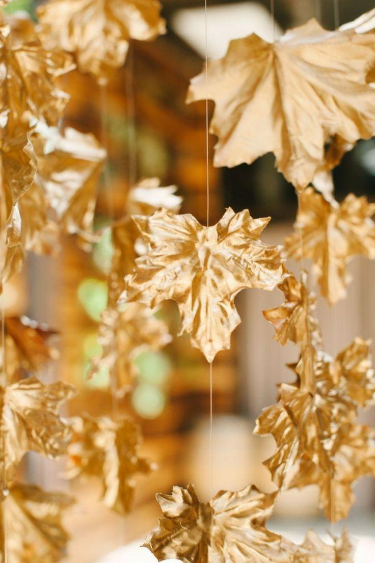 Wanddeko aus Herbstblättern golden gefärbt