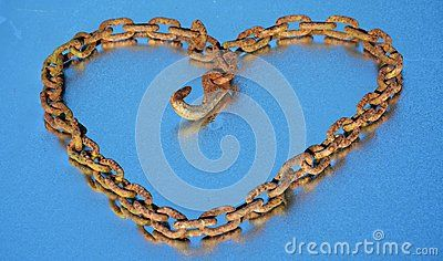 A heart like form made by a rusty and old chain on a blue background that reflects the blue of the sky. It suggests that hate can transform itself in love.