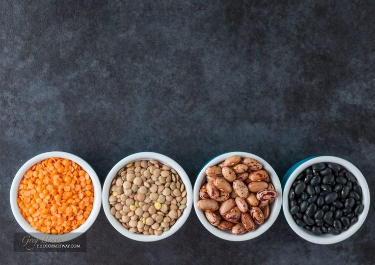 Red and brown lentils, heirloom beans, and black turtle beans on dark grungy surface. Top view with copy space.