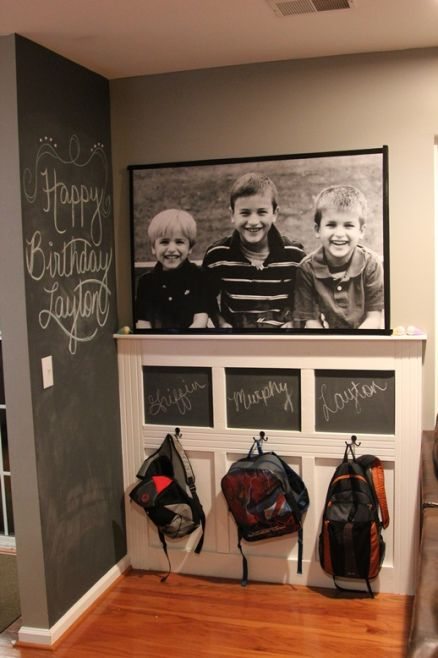 Simple diy wainscot backdrop with hooks and chalk board above each hook. Love this for an entryway.