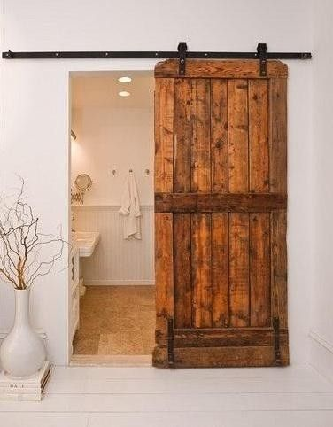 "The Brooklyn Home Company's rustic wood plank door and black track is striking against the white wall.  This style door is perfect for powder rooms placed in main living areas and solves the pesky design quandary we often hear: ""How do I hide the bathroom?!"" Closed, the door looks more like a textural element complimenting wood ceiling beams than an entry to the loo."