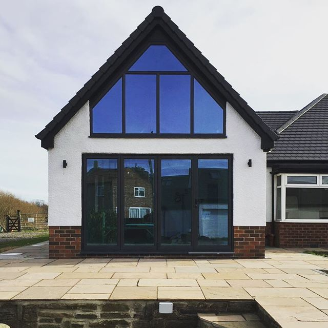 Gable End Aluminium Bi-Folding Doors & Angled Frame Windows in Anthracite Grey on a beautiful rendered home with Pilkington K Active Blue Glass with Heat Reflection  Supplied & Installed by National Window Systems. Contact us for a quote on 01325 381630 or sales@nationalwindowsystems.co.uk  Shaped Windows / Angled Windows / Gable End Windows / Bi-Folding Doors / Bi-Folds / uPVC / Aluminium / Rendered House / Home / Doors / Conservatories / Extension / Glazed / Heat Reflective Glass