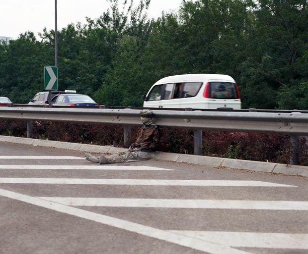 Liu Bolin sits on a road