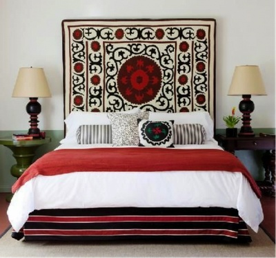 suzani headboard with red and black bedding. Painted chair rail in green.