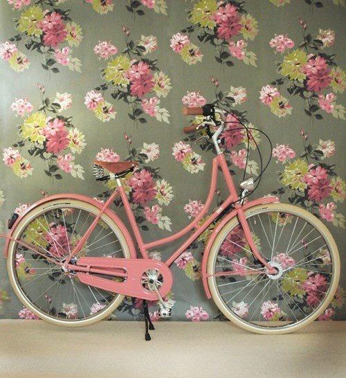 Vélo rose bonbon sur papier peint fleuri et délicieusement désué