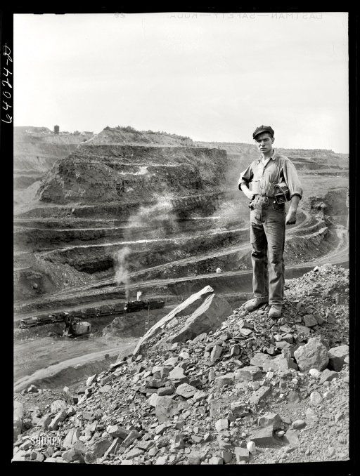 """August 1941. """"One end of the Hull-Rust-Mahoning pit, largest open pit iron mine in the world, near Hibbing, Minnesota. The pit is two and a half miles long, three quarters of a mile wide and about four hundred feet deep.""""  wem"""