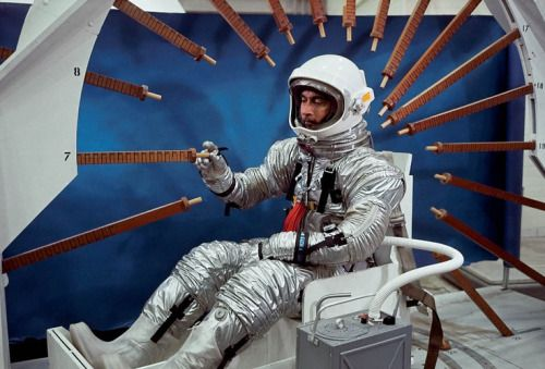 Astronaut John Young tests a spacesuit's range of motion, using rulers attached to the inside of a space capsule frame. Dallas, Texas, 1964. Photo by Ralph Morse.