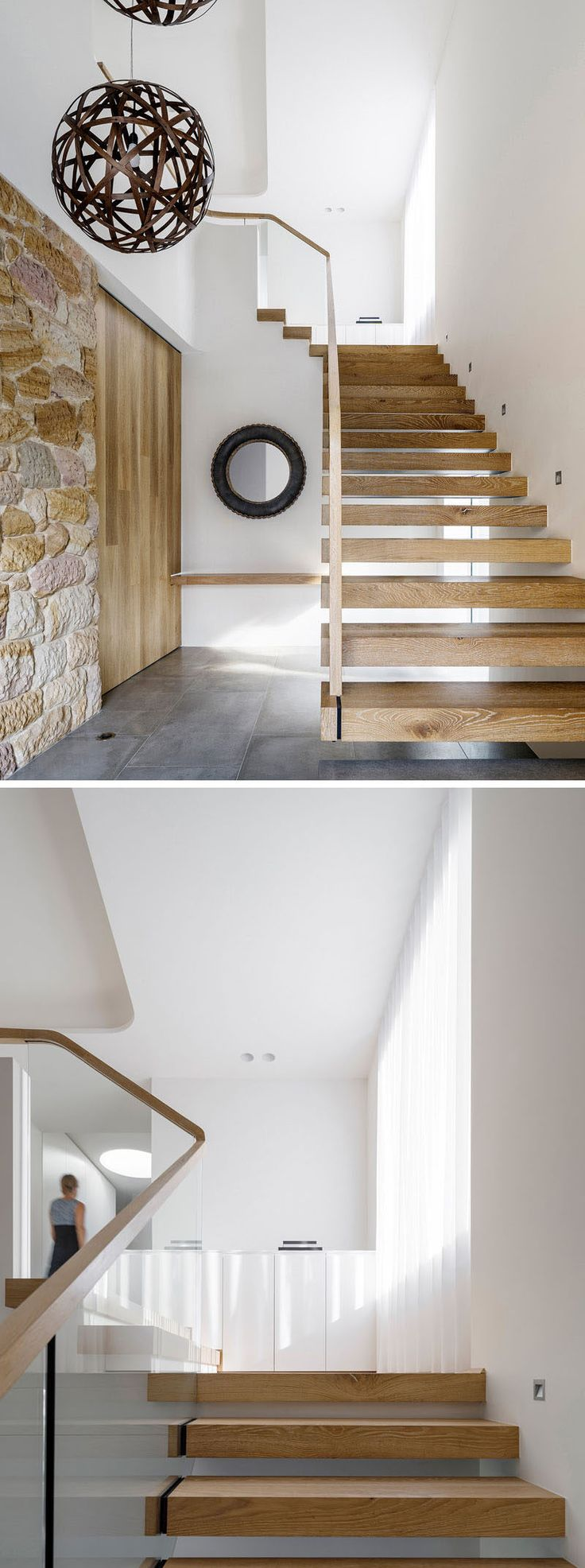 To the left of these modern wood and glass stairs is a recycled sandstone wall and large sliding wood door.