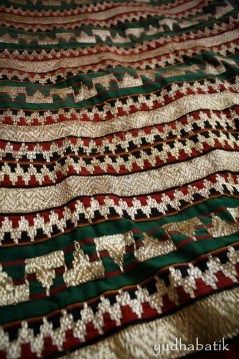 Tapis embroidery is  form by two panel of striped handwoven and then hand embroidered. Tapis embroidery, as decor with metallic thread, so it is not the mettalic thread that sewn into the fabric, but it is the cotton thread that sewn in a particular shape and design which holds the metallic thread. This one called 'tapis abung', named after the use of several ornaments such as Lampung typical headdress or 'siger' - Lampung, Sumatera