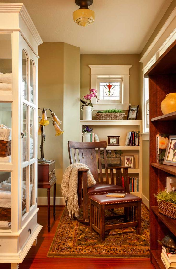 A period rocking chair and footstool turn this upstairs nook with built-in shelves into a cozy study space.