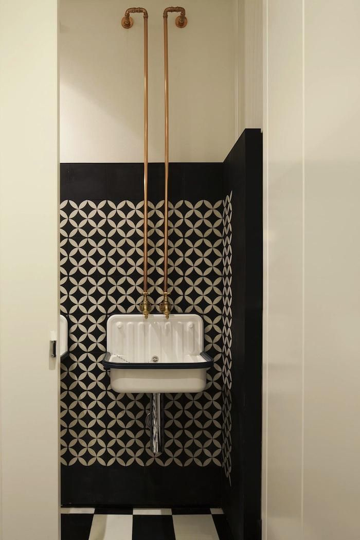 A humble bucket sink in the Old Library Restaurant washroom, designed by Australian firm Hecker Guthrie, is elevated by the addition of exposed copper piping and a painted wall mimicking tiles.