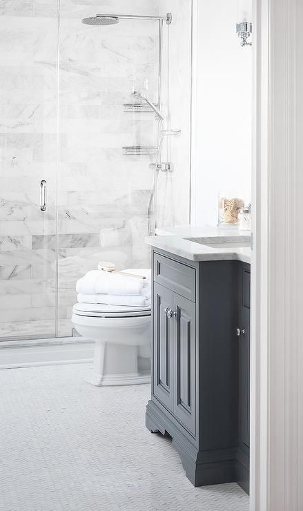 Beautiful bathroom features a dark gray vanity topped with carrera marble atop a white marble herringbone tile floor.