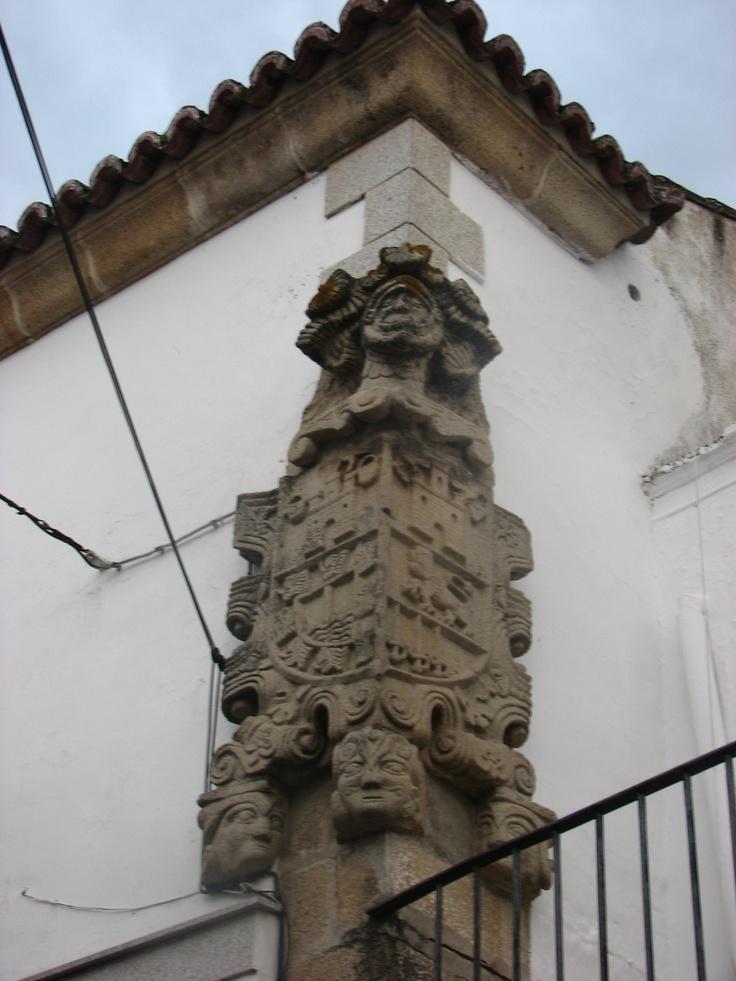 Curioso escudo esquinado en Navas del Madroño con elementos que recuerdan a motivos aztecas o mayas. A su derecha se encuentra la casa de los portales.