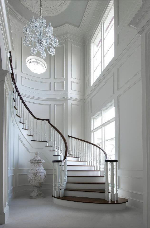 Ornate staircase, white paneled walls and a crystal chandelier.