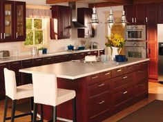 """Flexible Palette """"Keeping a kitchen neutral allows you to personalize it to reflect your style,"""" says IKEA spokesperson Mary Ann Barroso. """"This RAMSJÖ kitchen in red-brown can be matched to be on trend with lavenders, purples and mauves — we have a kitchen in our showroom accessorized that way right now."""" The real treat in this otherwise traditional kitchen is the unexpected light fixtures: IKEA's industrial-chic OTTAVA pendant lamps in aluminum, with shades made of mouth-blown glass."""