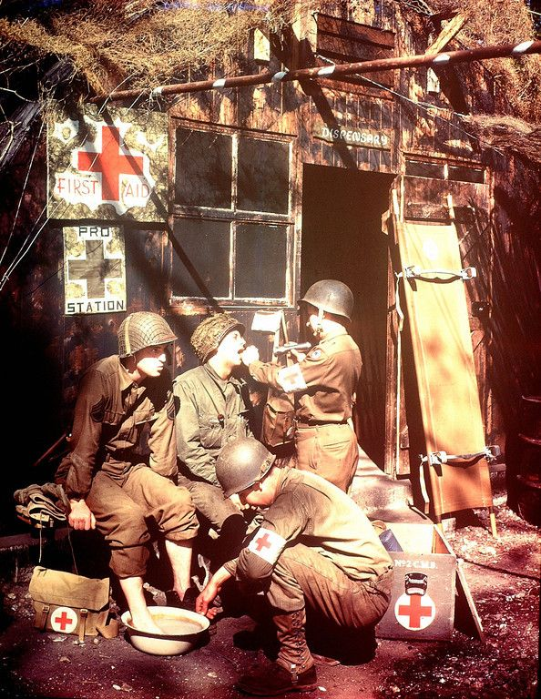 U.S. Army Medics treating two GIs at a first aid post in southern England in 1944. The soldiers are among the troops due to embark for the invasion of Normandy.
