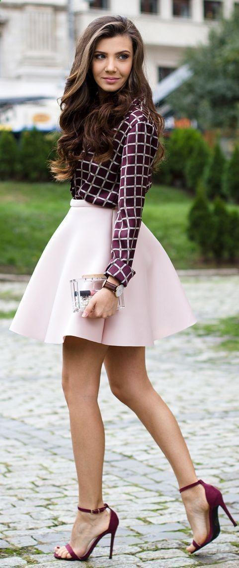 Acheter la tenue sur Lookastic: lookastic.fr/... — Jupe évasée rose — Montre en cuir brune foncée — Sandales à talons en daim pourpres — Chemisier boutonné à carreaux pourpre — Pochette transparente