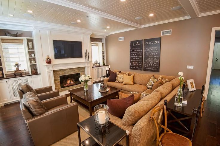 A tan sectional sofa and leather club chairs combine to create an inviting seating area in this spacious living room. A white paneled ceiling makes the space feel polished while built-in shelving around the windows provides storage and depth to the room. A modern tiled fireplace with a traditional white mantel is the finishing touch to the space.