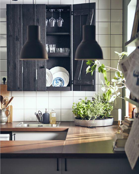 Se quiser uma cozinha exclusivamente tradicional, as bancadas em madeira e os móveis a combinar ajudam a completar o ambiente. Aqui, escolhemos um armário de parede rústico em preto e candeeiros de estilo industrial.