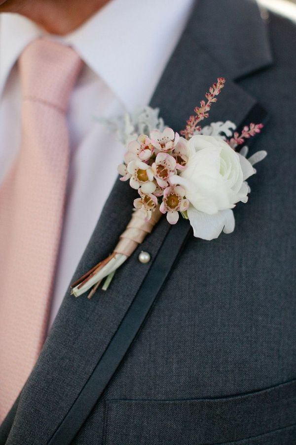 It's the details that make the difference. Make sure your groom has small touches on his boutonniere that complement your wedding color palette