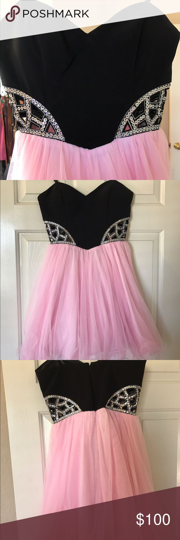 Pink and black homecoming dress Strapless (built in padding) black and pink dress. Two sequin cut outs on both sides of dress. 4 layers (meaning it is poofy). Only worn once. Blondie Nites Dresses Prom
