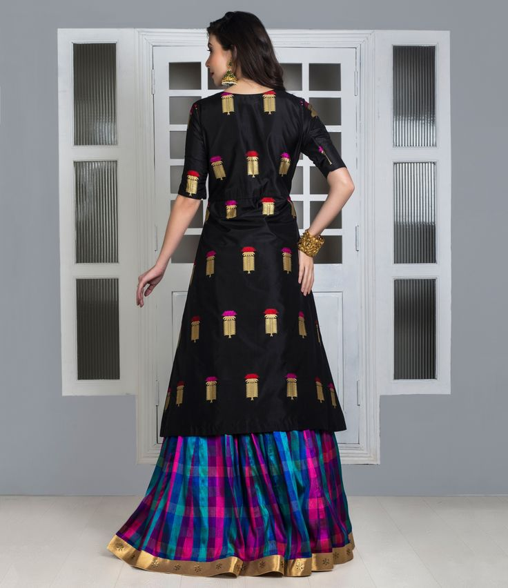 Black Pure silk long top choli with multicoloured Madras checks pure silk lehenga. This offbeat combination of weaves and colours is modest in look without a dupatta and ideal for someone who wishes to wear a lehenga but cover the waist and hip area at the same time. The plant shaped weave on the top and bright rush of colours in the Lehenga is surely one of a kind combination.