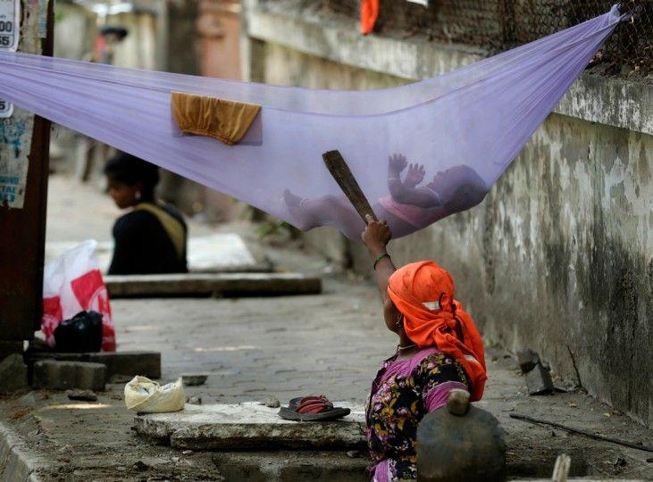 Une femme essaie de calmer son enfant qui pleure tout en nettoyant une bouche d'égout. La photo a été prise à Bombay, en Inde. Près de 800 millions de personnes vivent dans la pauvreté à travers le pays.