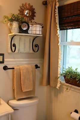 Shelf and towel bar above toilet maximizes storage space and looks nice.  The Butlers: Bathroom Reveal