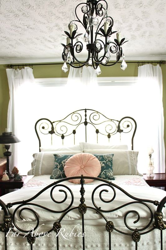antique style wrought iron bed frame with matching black chandelier