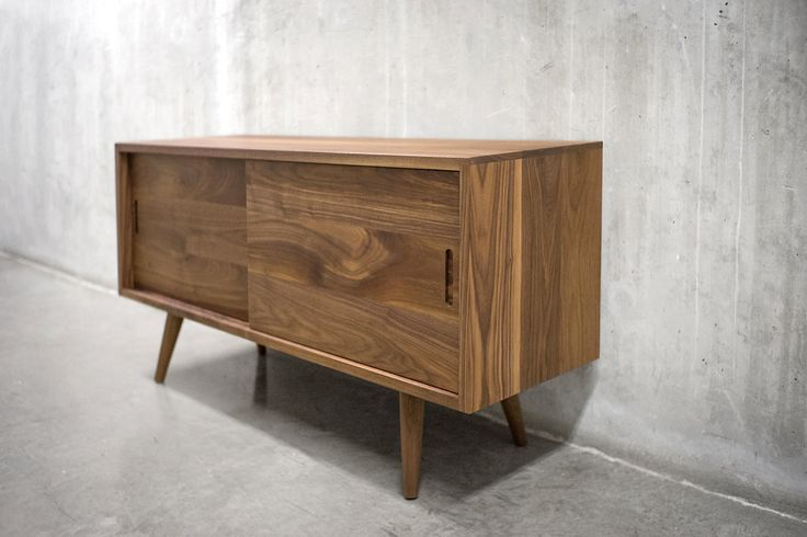 This Solid Black Walnut Sideboard/ Credenza will make a great addition to your modern home. This versatile item features two sliding doors and