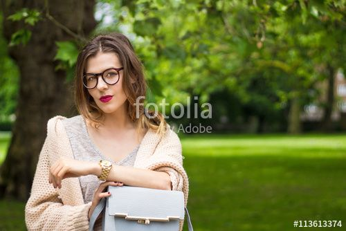 Attractive young girl sitting in the park